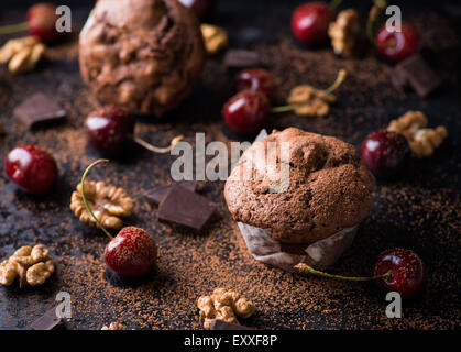 Chocolate muffins on dark background, cocoa powder, walnuts, cherries and chocolate chunks as decoration, selective - Stock Photo