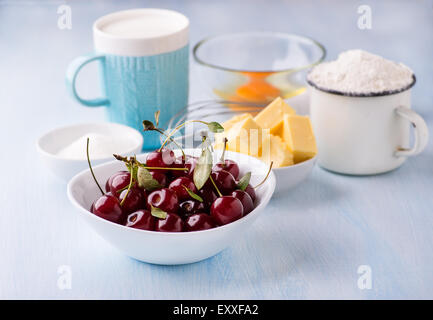 Cup of flour, butter, cherry, egg and milk. Ingredients for baking. Selective focus - Stock Photo