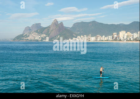 RIO DE JANEIRO, BRAZIL - MARCH 22, 2015: A pair of stand up paddle enthusiasts make their way along the water at - Stock Photo