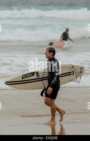 Two men walk oppisite directions with their surf boards at a beach in Newcastle.    Credit: Euan Cherry - Stock Photo