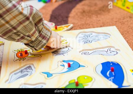 Little child puts the simple puzzle on the floor. Playing on floor. - Stock Photo