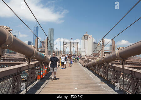 NEW YORK - May 30, 2015: People enjoying a walk along Brooklyn Bridge in New York city. - Stock Photo