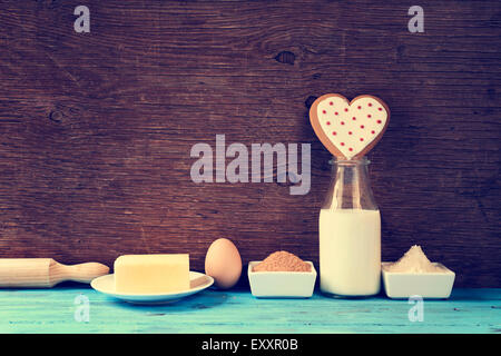 a heart-shaped cookie and the ingredients for cook it, such as milk, eggs, flour, butter and sugar on a blue rustic - Stock Photo