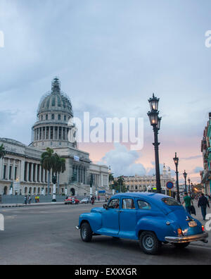 A vintage blue car drives along at dusk in from of the capitol building in Havana, Cuba - Stock Photo