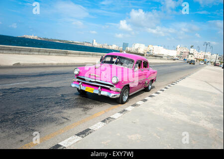HAVANA, CUBA - MAY 18, 2011: Classic pink American taxi drives along the waterfront road of El Malecon in Central - Stock Photo