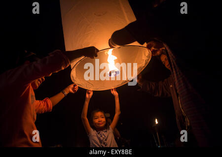 CHIANG MAI, THAILAND - OCTOBER 25, 2014: Group of Thai people launch a sky lantern on the night of the annual Yi - Stock Photo