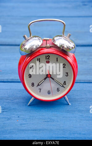red old style alarm clock on blue wooden garden table - Stock Photo