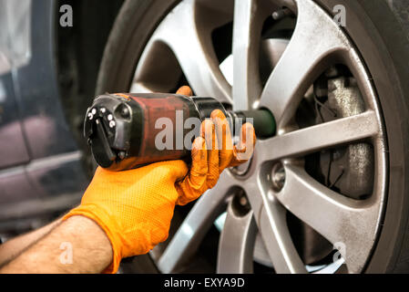 Mechanic working on a car wheel tightening or loosening the bolts on the hub and rim with an electric power tool, - Stock Photo
