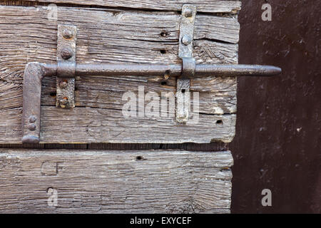 Rustic metal bolt on a weathered wooden door. - Stock Photo