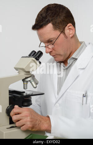 Mature scientist or associate professor performs microscopy - Stock Photo