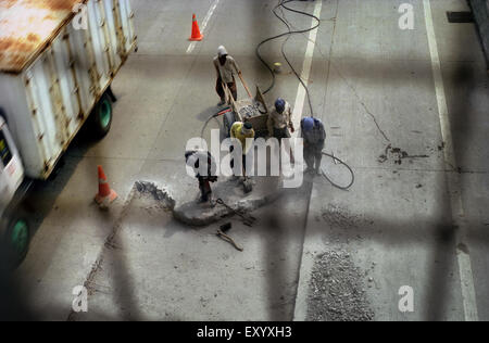 Construction workers doing maintenance work at freeway in Tanjung Priok, Jakarta, Indonesia. - Stock Photo