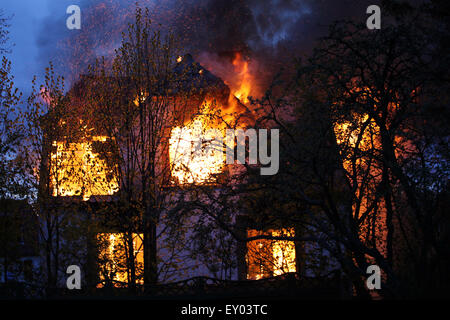 House on fire with heavy flames and dark smoke. Wild blaze - Stock Photo