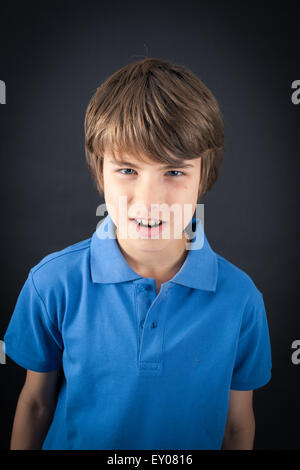 Handsome boy doing different expressions in different sets of clothes: angry - Stock Photo