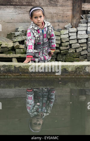 Little girl reflected in the village pool, Huanggang Dong Village, Guizhou Province, China - Stock Photo