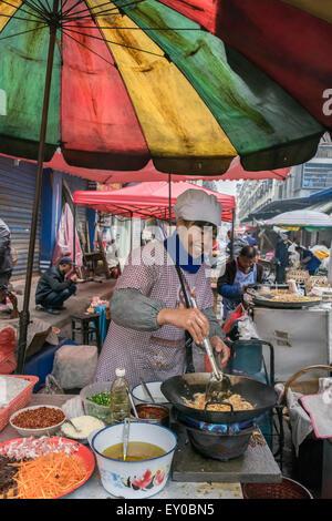 Woman cooking stir fry, Rongjiang Market, Guizhou Province, China - Stock Photo