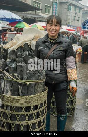 Woman selling baskets of charcoal, Rongjiang Market, Guizhou Province, China - Stock Photo