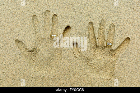 Two Hand shapes in the sand. Each hand has a  golden wedding ring on the fourth finger. - Stock Photo