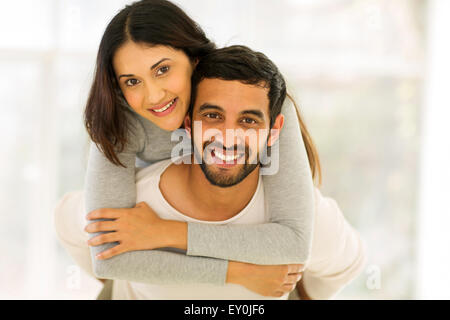 happy young Indian couple having fun with piggyback indoors - Stock Photo