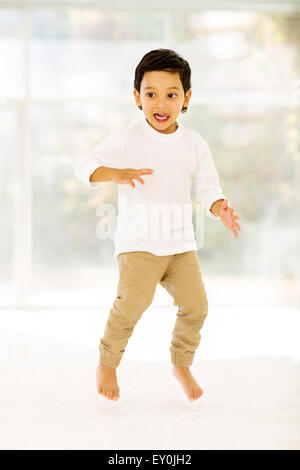 playful little Indian boy jumping on bed at home - Stock Photo