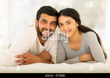 beautiful young Indian married couple lying on bed - Stock Photo