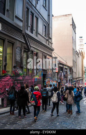 Young tourists admiring the street art displayed in Hosier Lane, Melbourne, Australia - Stock Photo