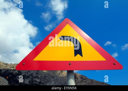 A road sign indicating left turning bend ahead - Stock Photo