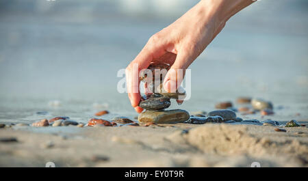 Hand arranging stone stack on beach, concept of balance and harmony. - Stock Photo