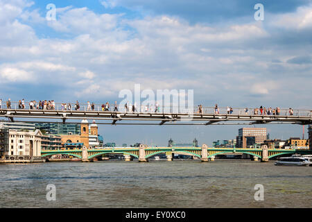 London Millennium Footbridge, nicknamed also 'Wobbly Bridge' and unrecognizable people walking over the Thames river. - Stock Photo