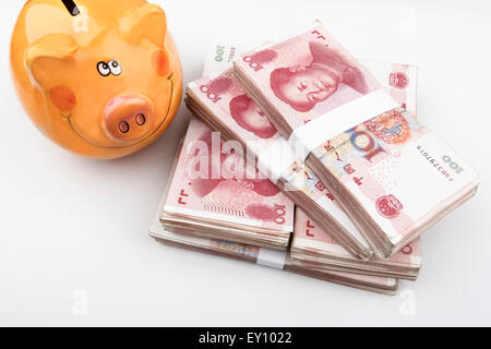 Chinese 100 RMB banknotes Stacked, with a happy piggy bank in the left top of the picture.