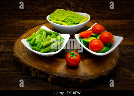 Vegetables on a dark wooden background. Salads, avocado, green beans. - Stock Photo
