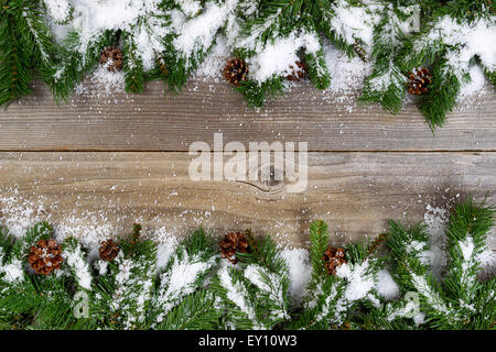 Christmas border, top and bottom of frame, with pine tree branches, cones and snow on rustic wooden boards. Layout - Stock Photo