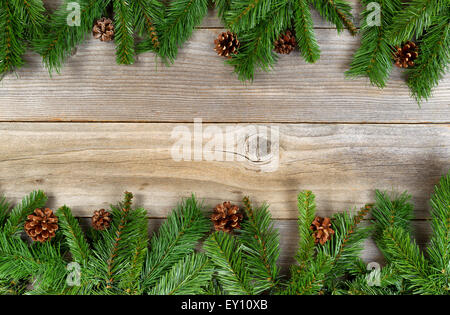 Christmas border, top and bottom of frame, with pine tree branches and cones on rustic wooden boards. - Stock Photo