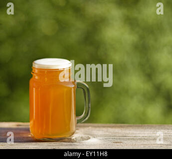 Pint of golden beer on rustic wood with blurred out green trees in background. Freshly poured to enjoy the outdoors. - Stock Photo