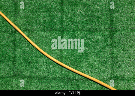 Bright yellow hose on a vivid green piece of astroturf - Stock Photo
