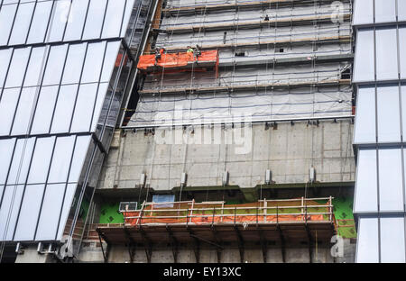 Workers on scaffolding, construction of glass building next to High Line. NYC, Manhattan, USA. - Stock Photo