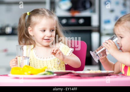 Cute little children drinking water at daycare - Stock Photo