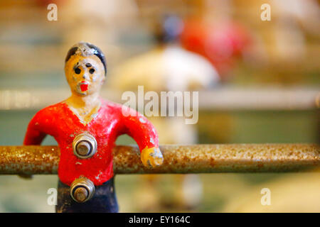 A old table top football player close up. Known as Foosball or babyfoot it's a much loved well worn player who's - Stock Photo