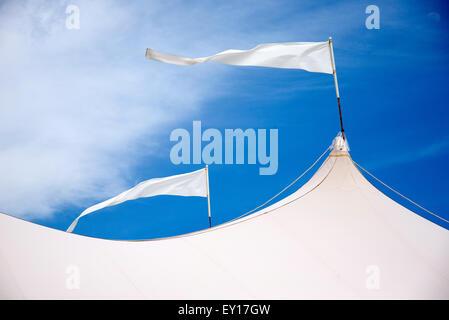 Marquee roof with white flags blowing in the wind against a blue sky - Stock Photo