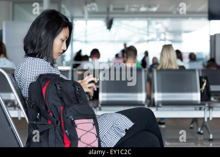 woman waiting for the plane at the airport - Stock Photo