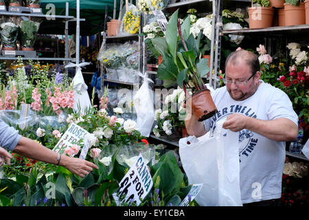 A  seller in Columbia Road flower market - Stock Photo