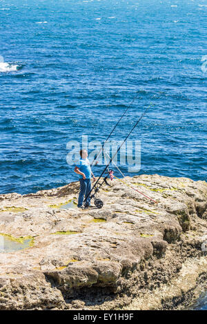 A lone fisherman sea fishing from rocks on the shore with long rods, Portland Bill, Dorset, south-west England - Stock Photo