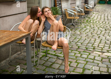 Two young best girlfriends sitting at the table of outdoors cafe and whispering. - Stock Photo