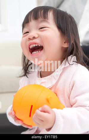 Baby girl holding piggy bank and smiling happily, - Stock Photo
