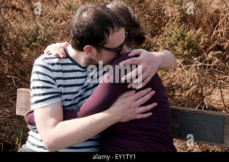 Couple with their arms around each other sitting on a bench - Stock Photo