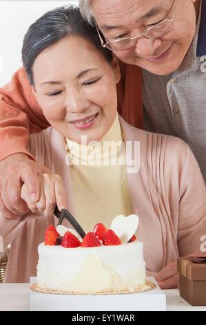 Senior couple celebrating birthday and cutting birthday cake Stock