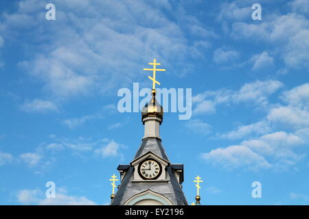 symbol of faith and believe shine crucifix on dome of orthodox church in blue sky - Stock Photo
