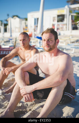 two handsome young man seated on the foreshore watching the sea at the beach in summertime - future, relax, tourism, - Stock Photo