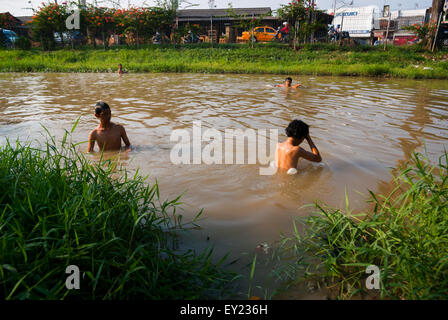 Local boys bathing on muddy canal in Jakarta. - Stock Photo