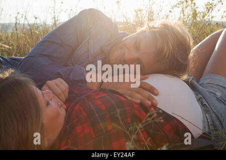 Young man listening to pregnant girlfriends stomach in field - Stock Photo