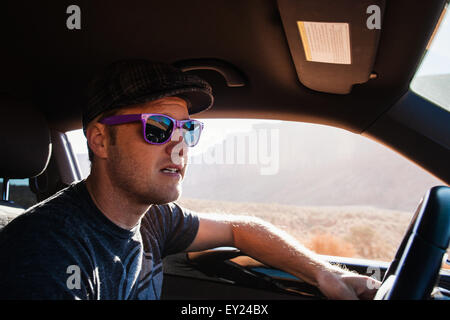 Man driving on road trip, Monument Valley, Utah, USA - Stock Photo